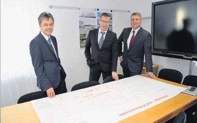 Führungsteam Projekt-HLS am Schreibtisch stehend