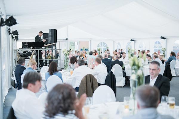 Blick ins vollbesetzte Zelt bei der Ansprache von Jürgen Brunner beim Firmenjubiläum 25 Jahre Projekt-HLS